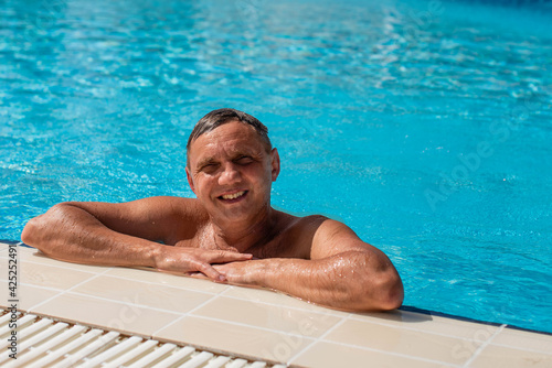 handsome guy half-naked cheerful man smiling laughing in blue water swimming pool Fototapeta