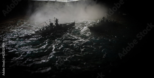 Leinwand Poster Silhouettes of a crowd standing at blurred military war ship on foggy background