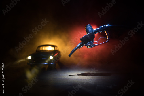 Fototapeta Creative concept. Silhouette of gasoline pistol miniature on dark toned foggy background. Close up. Industrial decorated elements on background. obraz