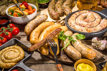 Assortment Of Different Fried Sausages. Set With Various Meat Bavarian, Frankfurt, German Grilled Sausages, Oktoberfest Or Summer BBQ Party Concept, Old Wooden Background Copy Space Top View
