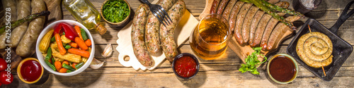 Fototapeta Assortment of different fried sausages. Set with various meat Bavarian, Frankfurt, German grilled sausages, Oktoberfest or summer BBQ party concept, old wooden background copy space top view obraz