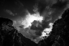 DRAMATIC CLOUDS ABOVE SLOPES. Black And White View On Sunlight Mountains In Clouds.
