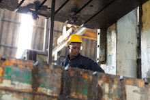 Young Black Male Engineer..checking Checking And Repair The Machine In Heavy Industry Manufacturing Facility. Service And Maintenance Of Factory Machinery. American African People.