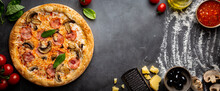 Tasty Mushrooms And Ham Pizza And Cooking Ingredients Tomatoes And Basil On Dark Background. Top View
