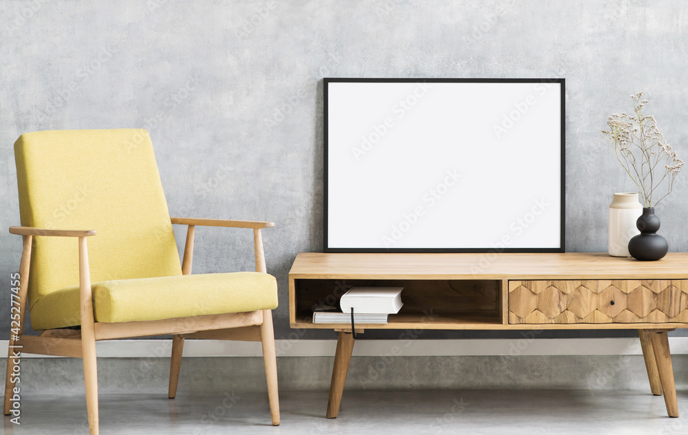 Fototapeta Blank picture frame mockup on gray wall. Living room design. View of modern style interior with chair. Home staging and minimalism concept