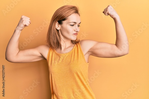 Foto Young caucasian woman wearing casual style with sleeveless shirt showing arms muscles smiling proud