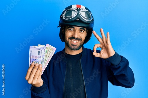 Obraz na plátně Young hispanic man wearing motorcycle helmet holding indian rupee doing ok sign