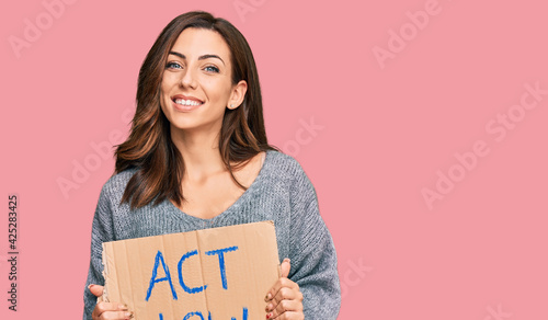 Foto Young brunette woman holding act now banner looking positive and happy standing