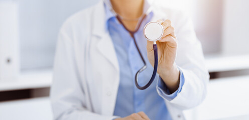 Unknown woman-doctor in blue blouse is holding stethoscope head while sitting in sunny clinic, close-up. Medicine concept