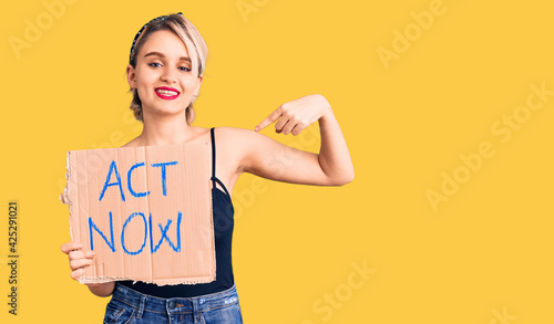 Foto Young beautiful blonde woman holding act now banner pointing finger to one self