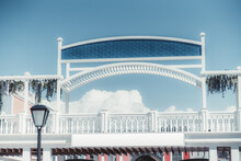 View From On The White Woodennarrow Pedestrian Bridge Decorated With An Arch And Hanging Plants, With Empty Placeholders Mockups For Captions: On The Top Over A Blue Pattern And A White On The Bottom