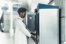 Side View Of A Fancy Young Black Female In Sunglasses And White Trench Using Indoor Atm To Withdraw Money; A Charming African Woman Buying A Railway Ticket Using A Modern Vending Machine On A Station
