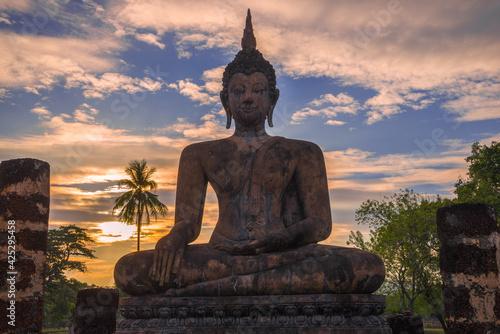 Obraz na plátně The sculpture of a sitting Buddha against a cloud sunset