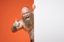 Fat Fun Obesy Pudge Chubby Overweight Tattooed Beard Man With Naked Torso Hold White Empty Blank Billboard Promotional Content Place For Text Image Show Thumb Up Gesture Isolated On Orange Background.