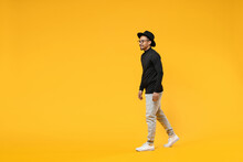 Full Length Side View Young Smiling Fashionable Fun African American Man 20s Wearing Stylish Black Hat Shirt Eyeglasses Walking Going Strolling Isolated On Yellow Orange Background Studio Portrait