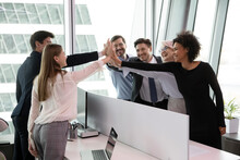 Excited Multiethnic Employees Colleagues Give High Five Celebrate Shared Work Success Or Achievement. Overjoyed Diverse Multiracial Businesspeople Triumph Engaged In Teambuilding Activity In Office.