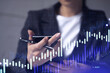A woman trader holding in the hands a smart phone and researching stock market to proceed right investment solutions. Internet trading and wealth management concept. Hologram Forex chart.