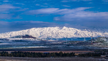 Beautiful Winter Landscape Of Golan Heights: View Of Snow-capped Mount Hermon On A Border With Syria And Lebanon - Israel's Only Ski Resort, With The Golan Heights Wind Energy Farm Turbines