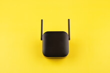 Repeater Wifi, Black Wifi Signal Booster On Yellow Background, Top View, Minimalism