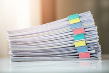 Piles Of White Papers Work Large Piles Of Papers Stacked Together. On The Desk In The Office With Colorful Clip. Documents That Are Not Finished In The Office. Business Concept.