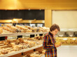 Teenager choosing bread from a supermarket.