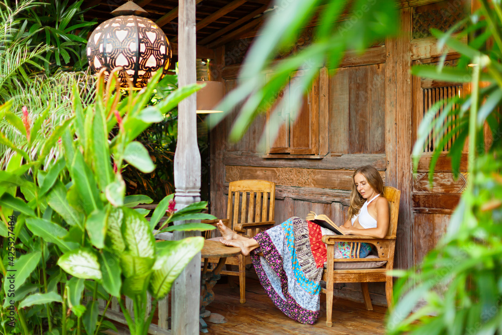 Fototapeta Attractive girl sit on open-air veranda of wood house with tropical garden view, read romance in paper book. Young woman relaxing in luxury villa on family summer vacation. Tropical island lifestyle. - obraz na płótnie
