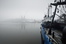 Tugboats And Fishing Boats (trawlers) Moored To A Pier In A Harbor. Thick White Fog. Latvia, Baltic Sea. Panoramic View. Service, Repair, Freight Transportation, Logistics, Industry, Commerce