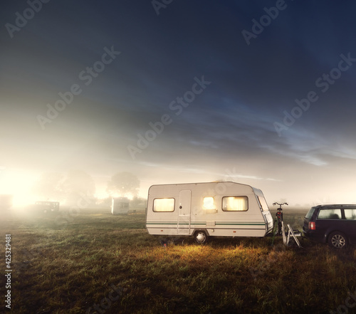 Foto White caravan trailer on a green lawn in a camping site