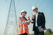 Engineer worker finger point at windmill model and electric pole in morning blue sky