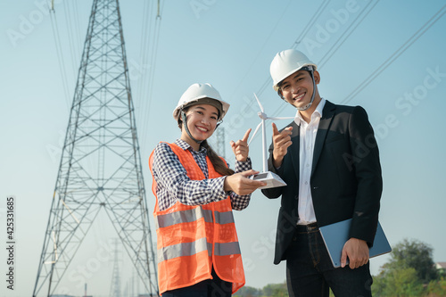 Fototapeta Engineer worker finger point at windmill model and electric pole in morning blue sky obraz