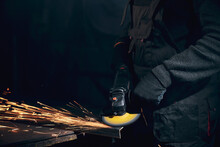 Worker In Black Gloves Working Angle Grinder With Metal.