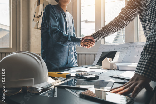 Obraz na plátně Architect shaking hands with clients to achieve agreement to work together at the office