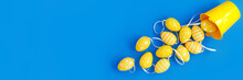 Concept Sweet Easter Symbols Colored Yellow Eggs And Buckets On Blue Paper Background.