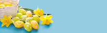 Beautiful Easter Card With Colorful Eggs And  Yellow Daffodils On Paper Blue Background.