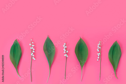 Fotografija Spring flowers of lily of the valley on a pastel pink background