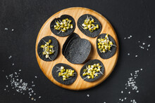 Black Nori Seaweed Chips With Mung Bean Sprouts On A Round Wooden Tray. Top View On A Black Background, With Grains Of Sea Salt.