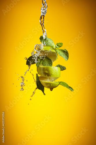 Fototapeta Fresh lime, mint, and ice in a splash. obraz na płótnie