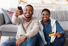 Black Couple Holding Remote Control And Credit Card