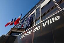 """Vue Extérieure D'une Mairie Française Avec Des Drapeaux Et Le Mot """"Hôtel De Ville"""" écrit En Français Sur La Façade"""