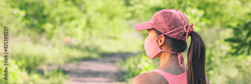 Mask covid-19 outside lifestyle woman walking at outdoor park wearing pink face cover for coronavirus prevention.