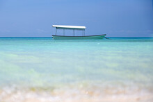 A Small White Boat For Walking Is Anchored Near The Shore With Clear Turquoise Water And White Sand. The Concept Of Recreation. Small Fishing Boat With Sunshade
