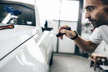 Car Detailing - Manual Worker With Battery Lamp Checking Polishing Quality In Auto Repair Shop. Selective Focus.