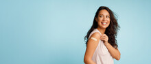 Woman Showing Vaccinated Arm With Bandage After Injection, Blue Background