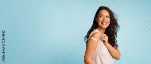 Billede på lærred Woman Showing Vaccinated Arm With Bandage After Injection, Blue Background