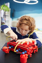 Vertical Portrait Of Cute Boy Building Robot During Engineering Class In Development School