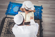 Muslim Child Learning To Read Quran With His Father