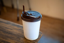 A Paper Cup Of Hot Coffee With Plastic Cap Placed On The Table