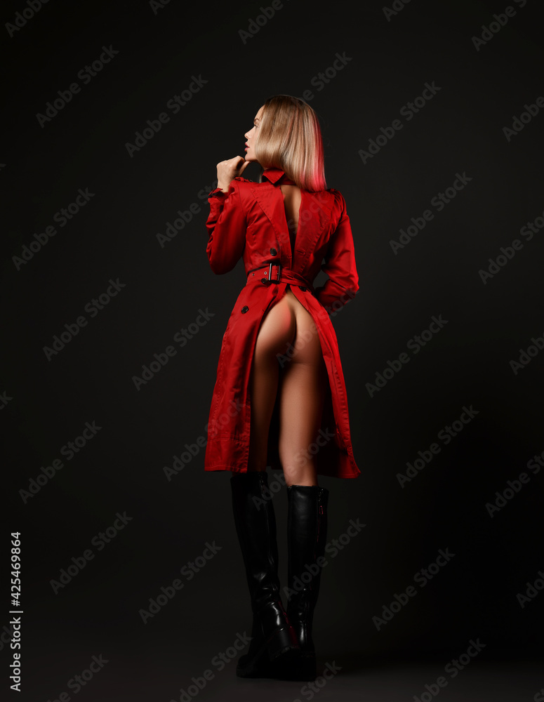 Fototapeta Back view of sexy gorgeous blonde woman in leather high boots and red unbuttoned coat standing backwards with butt naked over black background. Fashion, vogue, sexy stylish look for woman concept