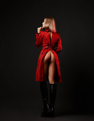 Back view of sexy gorgeous blonde woman in leather high boots and red unbuttoned coat standing backwards with butt naked over black background. Fashion, vogue, sexy stylish look for woman concept