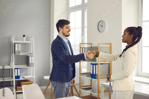 Happy manager getting acquainted and exchanging handshake with new client. Two diverse business people meet in office, shake hands, make agreement and thank each other for help and cooperation